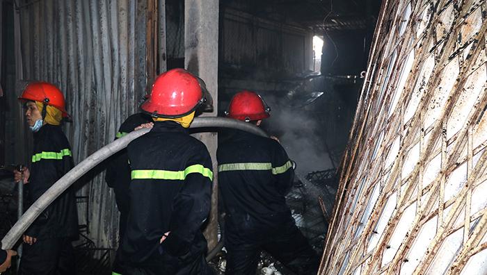 Cảnh sát cứu hoả phá cửa phun nước vào đám cháy.