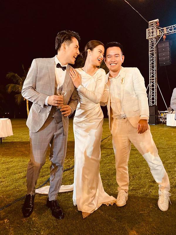Nhà thiết kế Lê Thanh Hoà kiễng chân để chụp ảnh với cô dâu, chú rể.