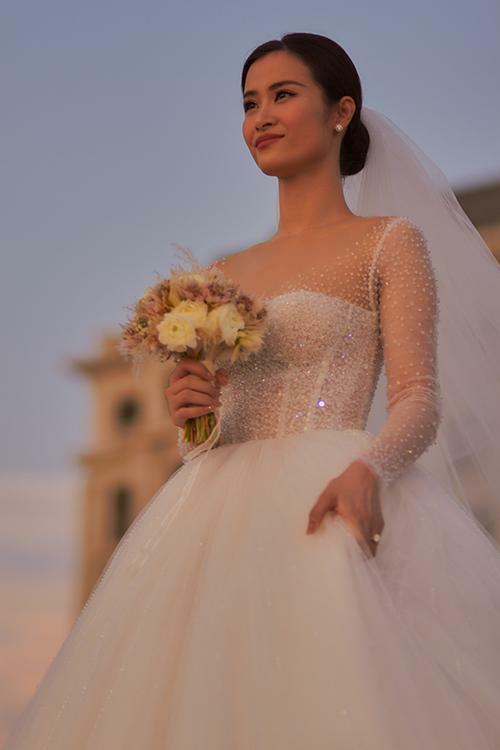 Nữ ca sĩ mong muốn chiếc váy cưới trong mơ sẽ có sự nhẹ nhàng, tôn vẻ đẹp mong manh, trong trẻo. Vì vậy, Chung Thanh Phong đã lấy cảm hứng từ giọt sương mai để tạo nên bộ đầm cưới được đính đá Swarovski trong suốt lấp lánh, phản chiếu ánh sáng theo từng chuyển động của cô dâu.