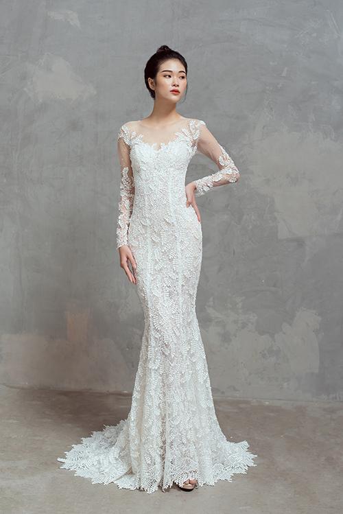 Váy có phom dáng đuôi cá, được khai thác từ chất liệu ren, có cổ illusion mờ ảo từ voan mỏng - xu hướng được ưa chuộng trong thời trang cưới hiện đại.