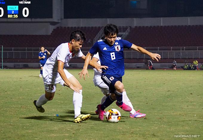 Các cầu thủ trẻ Việt Nam nỗ lực khóa chặt các ngòi nổ của Nhật Bản. Ảnh: H.N