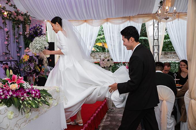 Ở lễ vu quy, chú rể giúp cô dâu nâng váy cưới đuôi dài.