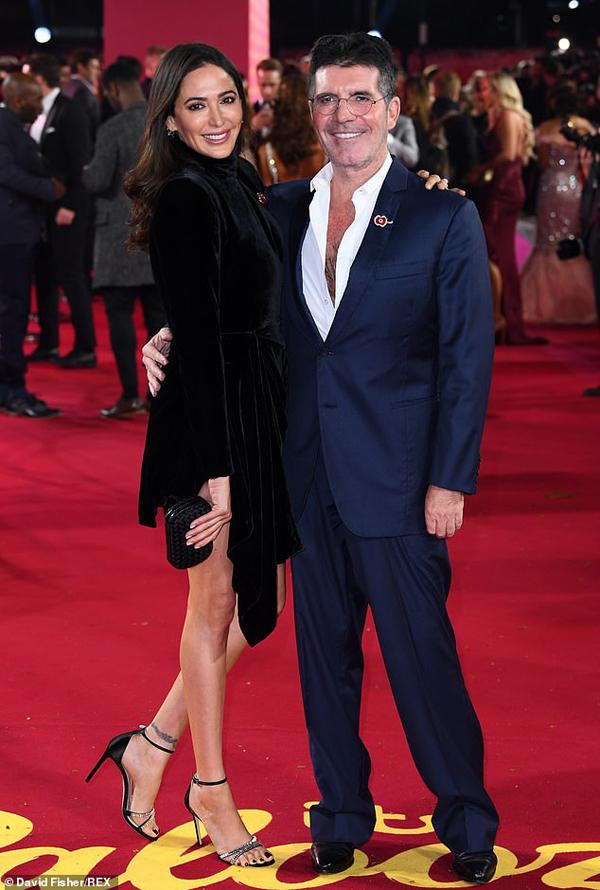 Simon Cowell và người bạn đời Lauren Silverman tình tứ tại sự kiện truyền hình quảng cáo ITV Palooza. Ông trùm truyền thông 60 tuổi phong độ trong bộ vest xanh kết hợp với sơ mi bỏ ngỏ cúc trong khi bạn gái mặc váy nhung khoe chân dài.