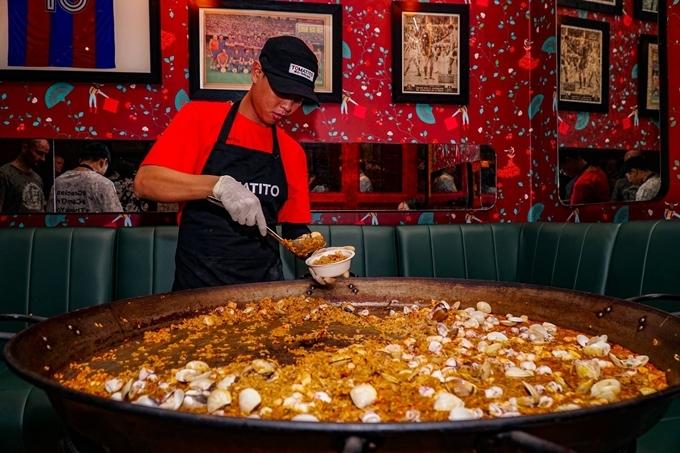 Thỉnh thoảng sẽ có màn biểu diễn chế biến món cơm pealla nổi tiếng xứ sở bò tót. Chảo cơm chiên hải sản, thịt, rau... lớnđặt giữa quán, nơi thực khách có thể vừa lấy thức ăn, vừa thoải máitrò chuyện cùng đầu bếp về món ăn.