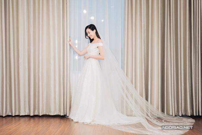 Váy cưới mang phom dáng chữ A nhẹ nhàng, có độ xòe nhẹ làm toát lên vẻ đẹp trong trẻo của hot girl Sài thành, được sử dụng kết hợp với lúp cưới dài.