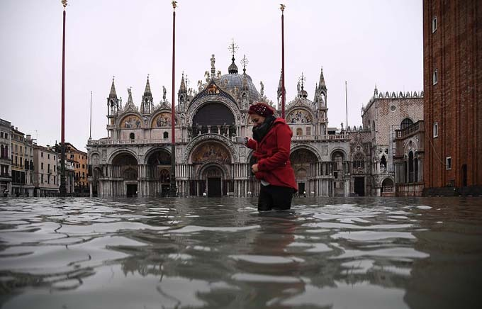 A woman crosses the flooded St Marks Square this morning where Venices 1,200-year-old basilica (pictured behind her) was flooded by the high tide