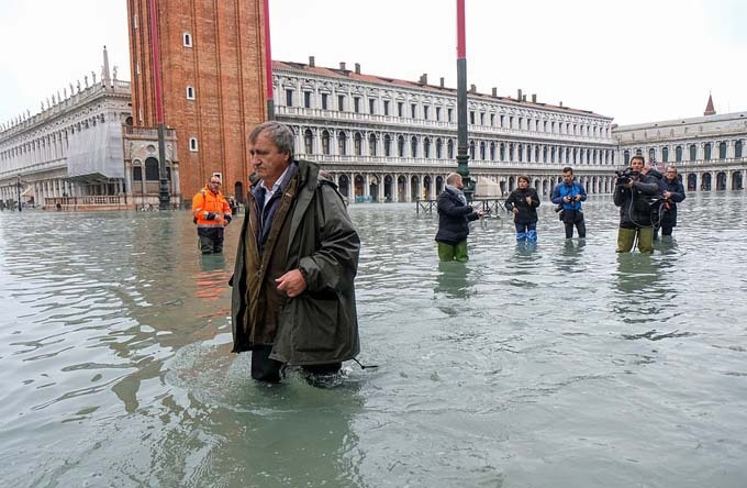 Wading in the water: The mayor of Venice, Luigi Brugnaro, walks in the submerged St Marks Square today as Venice responds to one of the worst episodes of flooding in its history - which the mayor has blamed on climate change