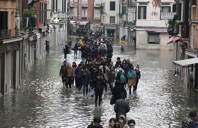 A crowd of people wade through a street in Venice today with hotels and shops on either side fearing damage from the flood