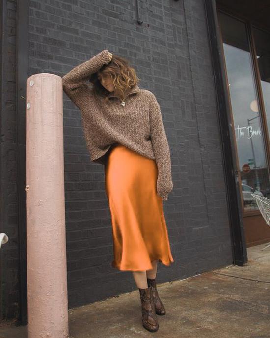Sự đối nghịch giữa nét óng ả của chân váy lụa, vẻ xù xì, to bản của áo len lại mang đến tổng thể lạ mắt và hấp dẫn nhiều chị em.