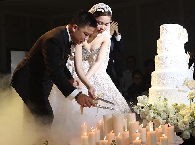 Đôi vợ chồng nắm tay nhau thắp nến hạnh phúc, bắt đầu các nghi thức quen thuộc trong tiệc cưới.