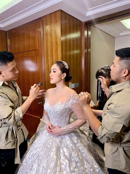 Quân Nguyễn (bìa trái) dặm lại phấn cho cô dâu. Pu Lê (bìa phải) thay đổi kiểu tóc Bảo Thy đôi chút với phần tóc uốn cong nơi má khi người đẹpthay váy cưới thứ 2.