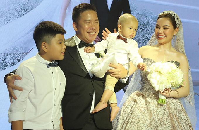 Cô dâu chú rể chụp ảnh cùng con trai cưng trong hôn lễ.