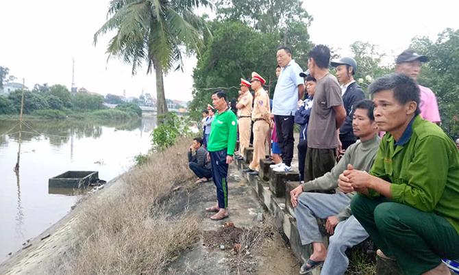 Người dân tập trung bên bờ sông xem tìm kiếm thi thể nạn nhân. Ảnh: H.L