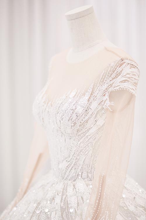 Phần cổ, tay váy đều được may lớp voan xuyên thấu, giúp phô diễn vẻ đẹp của cô dâu mà không làm mất đi sự ý nhị, duyên dáng.