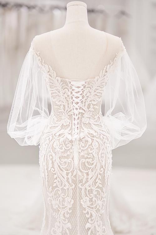 Đầm đón khách có chi tiết cổ V trễ vai, khoét lưng gợi cảm. Tay áo phồng theo xu hướng thời trang quý tộc, vương giả. Các hoạ tiết ren được nhà mốt 8X đắt đối xứng, làm toát lên vẻ yêu kiều, điệu đà của Bảo Thy.