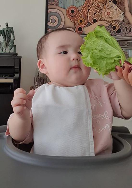 Bé đang trong giai đoạn ăn dặm nên được mẹ cho tiếp xúc và nếm thử nhiều loại rau quả, thức ăn khác nhau.