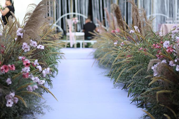 Lối dẫn lên lễ đường được trang trí với cỏ lau, các loài hoa đồng nội phù hợp concept tiệc sân vườn.