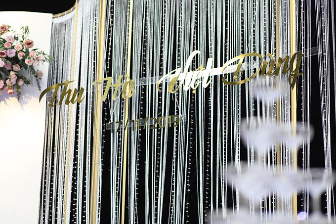 Sân khấu cưới được trang trí với hoa tươi và tên của cặp vợ chồng mang tông vàng đồng hiện đại.