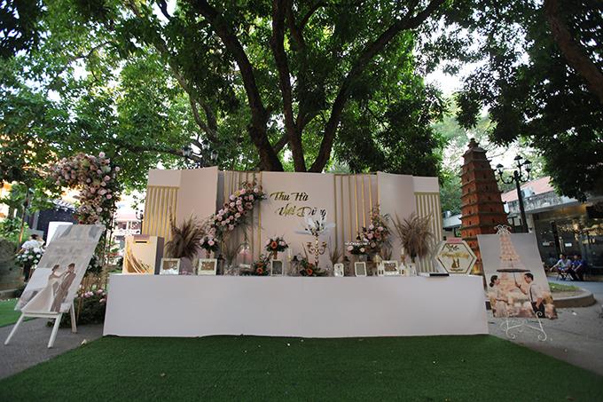 Bàn gallery bài trí hoa tươi, ảnh cưới chụp tại Paris của cặp vợ chồng. Thu Hà yêu thích tông trắng - hồng nên chọn các gam này làm màu chủ đạo để trang trí.