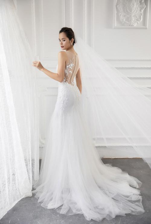 Nét đẹp nơi tấm lưng thon được ẩn hiện sau làn voan mỏng, chi tiết ren thêu tay tỉ mỉ, hàng cúc ngọc trai lấp lánh. Với chiếc váy đã nổi bật như vậy, kiểu tóc cô dâu bới đơn giản sẽ là sự kết hợpăn ý.