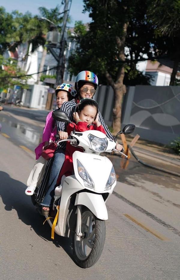 Hồng Nhung chở con đi học bằng xe máy.