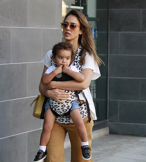 Bé Hayes 2 tuổi ngồi ngoan trong lòng mẹ, chăm chú mút ngón tay. Jessica Alba địu con bằng sản phẩm baby carrie 300 USD do công ty Honest của cô thiết kế và sản xuất.
