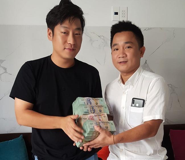 Anh Bùi QuốcTuấn đưa lại số tiền cho anh Seol Young Jin, du khách Hàn Quốc vào sáng 19/11. Ảnh: Đại Hiệp.