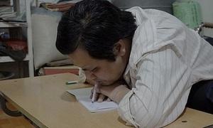 Người thầy ngồi xe lăn, viết chữ bằng miệng