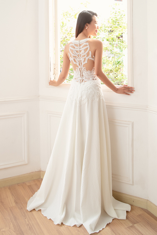 Mặt lưng váy giống như tác phẩm nghệ thuật điêu khắc với đường néthọa tiết tinh xảo, cầu kỳ, giúp thiết kế hút ánh nhìn của tân lang, khách mờitừ mọi góc độ.