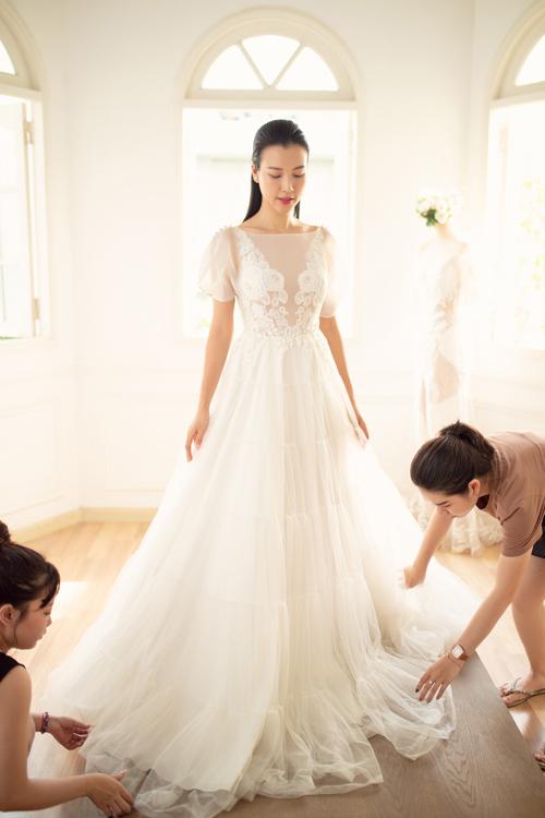 Hoàng Oanh thử tiếp váy cưới dáng A xòe nhẹ. Mẫu đầm được tạo từ nhiều lớp lang, có lớp ren ẩn dưới voan mỏng, tạo hiệu ứng ẩn hiện.