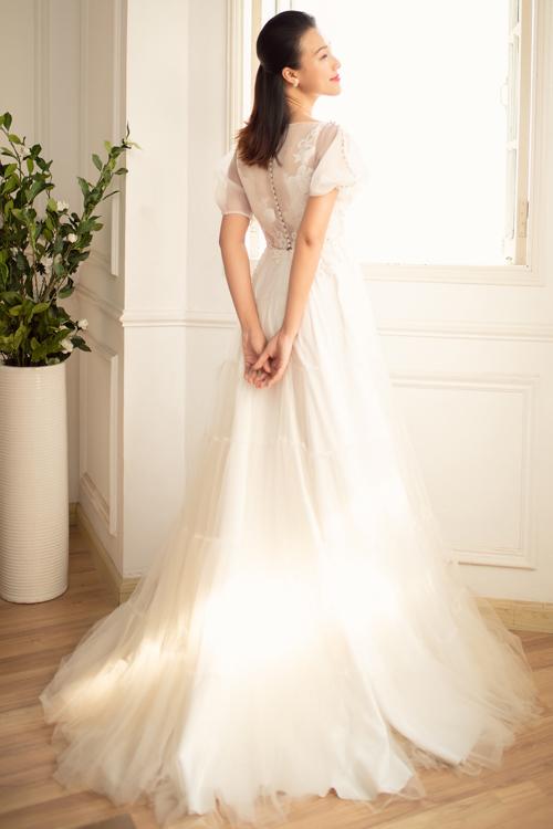 Lưng váy có hàng cúc ngọc trai và họa tiết ren ẩn hiện, giúp cô dâu tỏa sáng khi diệnváy cưới ở mọi khung hình.