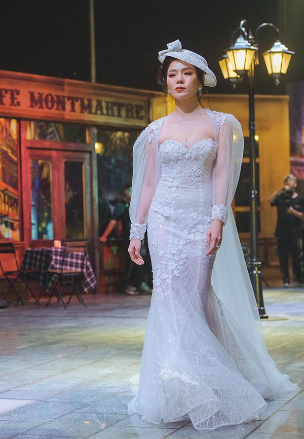 Nữ ca sĩ Giấc mơ có thật lộng lẫy trong bộ váybó sát, tôn ngực đầy. Đây là thiết kế thuộc bộ sưu tập áo cưới do ba nhà thiết kế Hoàng Hải, David Minh Đức, Kelly Bùi cùng thực hiện và được trình diễn tối qua.