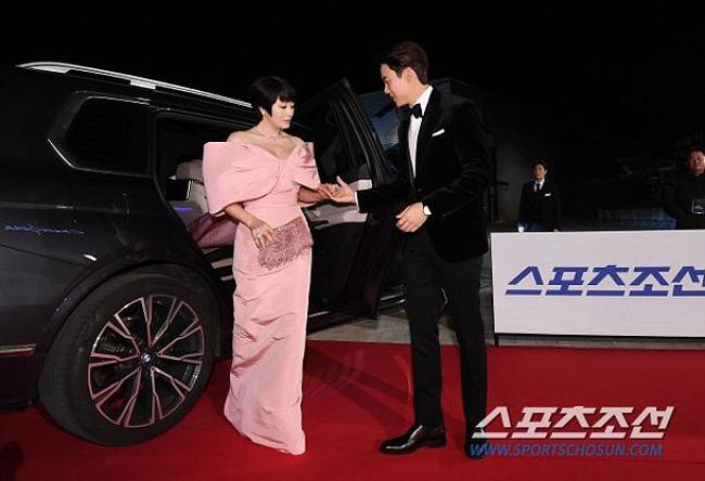 Chị đại Kim Hye Soo trở thành tâm điểm chú ý khi xuất hiện trên thảm đỏ Lễ trao giải Rồng Xanh tối qua 21/11 tại Seoul, Hàn Quốc. Nữ diễn viên 49 tuổi để tóc tém, mặc váy hồng rực rỡ, trông tươi trẻ như cô gái đôi mươi. Đón bước Kim Hye Soo và dìu cô trên thảm đỏ là đàn em  Yoo Yeon Seok.