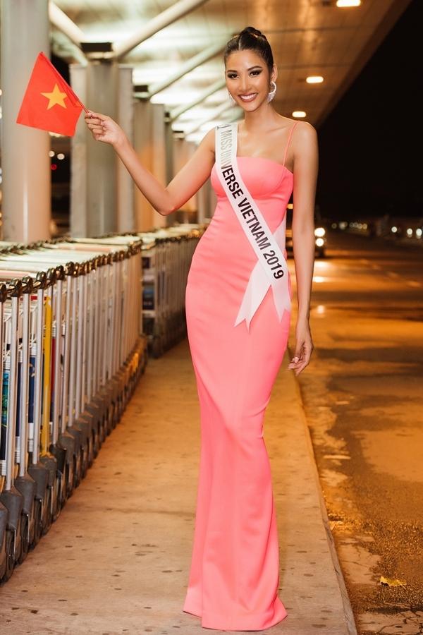 Hoàng Thùy diện đầm ôm khoe dáng, cầm cơ vẫy chào khán giả trước khi lên đường. Năm nay 27 tuổi, người đẹp được khán giả biết đến qua danh hiệu: quán quân Vietnams Next Top Model 2019, Á hậu 1 Hoa hậu Hoàn vũ Việt Nam 2017. Cô được trao quyền đại diện Việt Nam dự thi Miss Universe 2019 tại Mỹ. Hoàng Thùy cao 1,77m, nặng 59 kg, số đo 84-60-96.