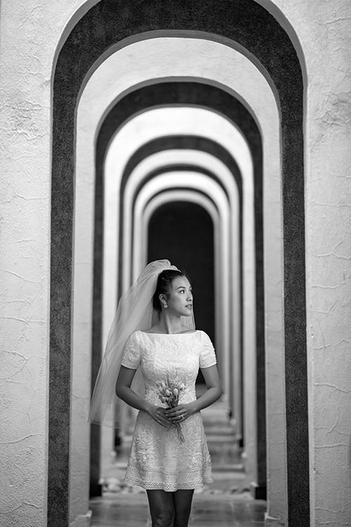 Mẫu đầm có tay ngắn, cổ thuyền đơn giản. Để tạo dựng điểm nhấn cho tấm áo cưới, NTK đính kết hạt lấp lánh, cườm tạo họa tiết dọc thân. Bộ cánh được kết hợp với lúp cưới ngắn, hướng đến sự trẻ trung, hiện đại.