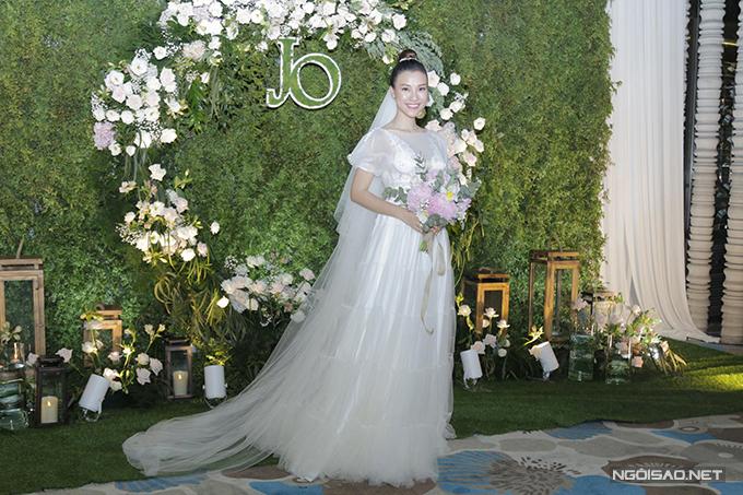 Cô dâu diện các váy cưới đến từ NTK Trương Thanh Hải cho ngày trọng đại. Cô dâu chọn trang trí tiệc từ nhà hàng. Không gian cưới được tô điểm với hoa hồng, các chi tiết bằng gỗ, nến trắng, gợi nhắc tới phong cách rustic, phù hợp với lễ cưới ở sân vườn.