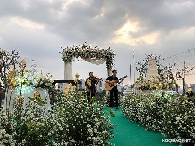Trong lúc chờ tới giờ cử hành hôn lễ, khách mời được lắng nghe những giai điệu du dương từ ba nhạc. Không gian cưới ngoài trời được tô điểm với cúc họa mi dọc lối đi - loài hoa đang tới mùa nở rộ. Cổng cưới hình chữ nhật được trang trí với hoa hồng tươi và các dải lụa.
