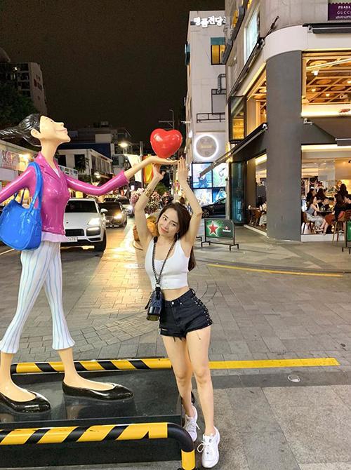 Quỳnh Nga tạo dáng trẻ trung ở khu phố Hongdae (Seoul, Hàn Quốc). Người đẹp cá sấu chúa diện trang phục thoải mái dạo phố và thích thú với món cà phê ở xứ sở kim chi.