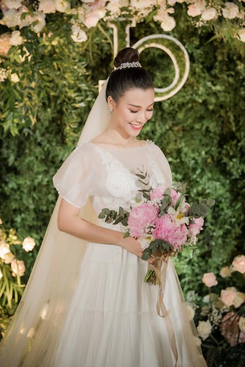 Váy đầu tiên mà cô dâu diện để đón khách có dáng chữ A xòe nhẹ. Mẫu đầm được tạo dựng từ nhiều lớp lang, có lớp ren ẩn dưới voan mỏng, tạo hiệu ứng thị giác ẩn hiện.