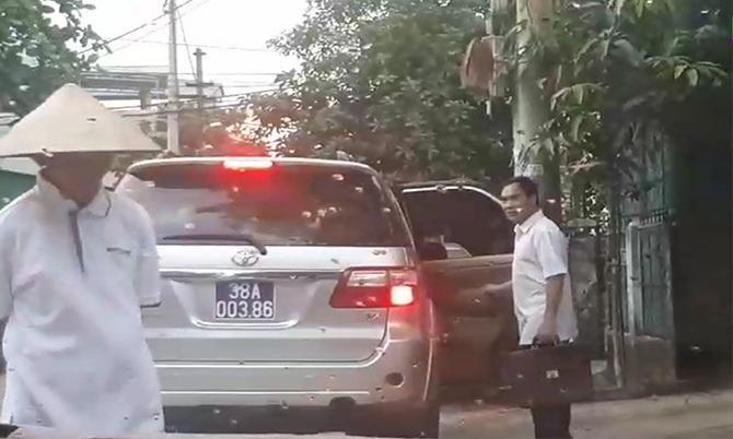 Xe công vụ của TAND Hà Tĩnh đón ông Nguyễn Văn Thắng (áo trắng, bên phải) tại cổng phụ ngôi nhà của ông này ở đường Nguyễn Công Trứ. Ảnh: D.T