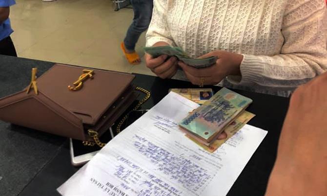 Nữ du khách kiểm tra lại số tiền bị bỏ quên. Ảnh: S.T.