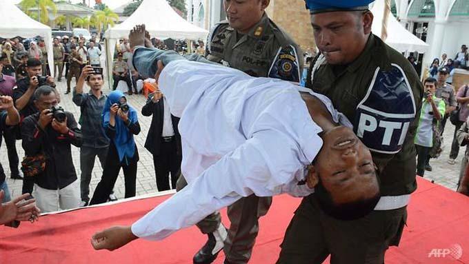 Chàng trai ngất xỉu giữa chừng khi đang nhận án phạt 100 roi hôm 5/12. Ảnh: AFP.