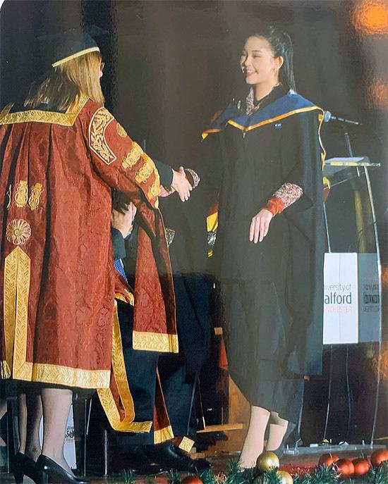 [Caption Sáng ngày 5/12, Lê Âu Ngân Anh đã chính thức được gọi tên lên nhận bằng Thạc sĩ danh danh giá trường ĐH Salford University (ở Manchester, Anh). Cô diện đồng phục của trường, tự tin lên sân khấu nhận bằng, phát biểu về cảm xúc của mình trong ngày tốt nghiệp.
