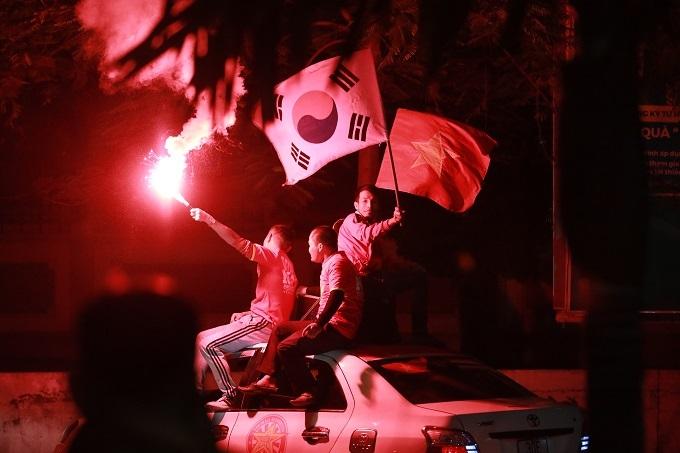 Một nhóm CĐV ngồi trên nóc xe ô tô, đốt pháo sáng ăn mừng. Ảnh: Nguyễn Ngoan