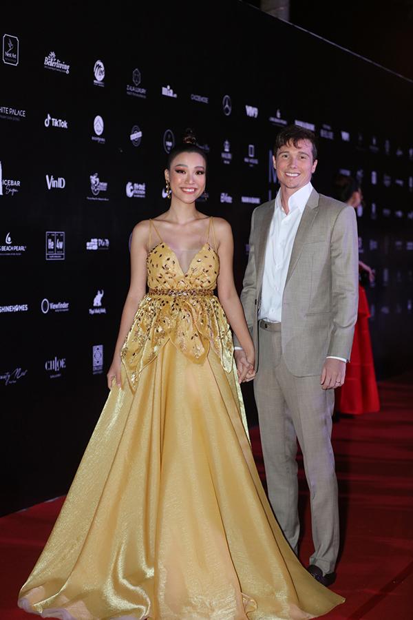 Á hậu Hoàng Oanh nắm chặt tay chồng mới cưới trên thảm đỏ. Cô đảm nhận vai trò MC của đêm chung kết Hoa hậu Hoàn vũ Việt Nam 2019.