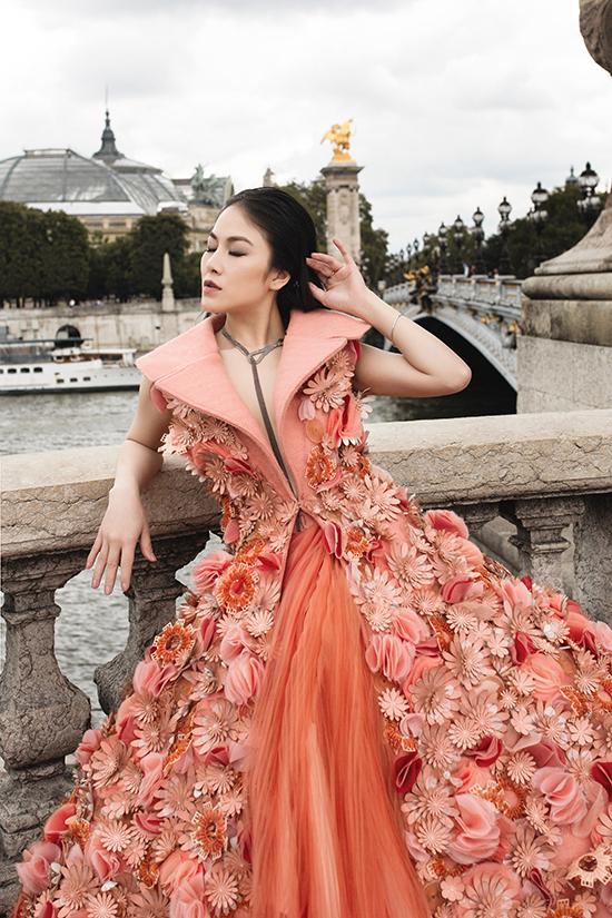 Đầm cổ điển tông cam ổi bật trở nên rực rỡ hơn bởi được đính hàng trăm cánh hoa 3D trên tùng xoè rộng lớn.