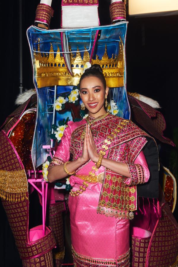 Người đẹp Lào diện váy truyền thống đính mô hình chùa phía sauvà cài hoa champa.