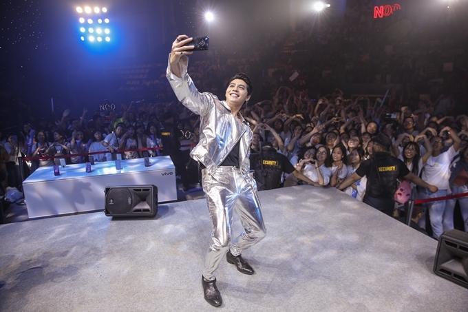 Noo Phước Thịnh cầm điện thoại selfie cùng fan.