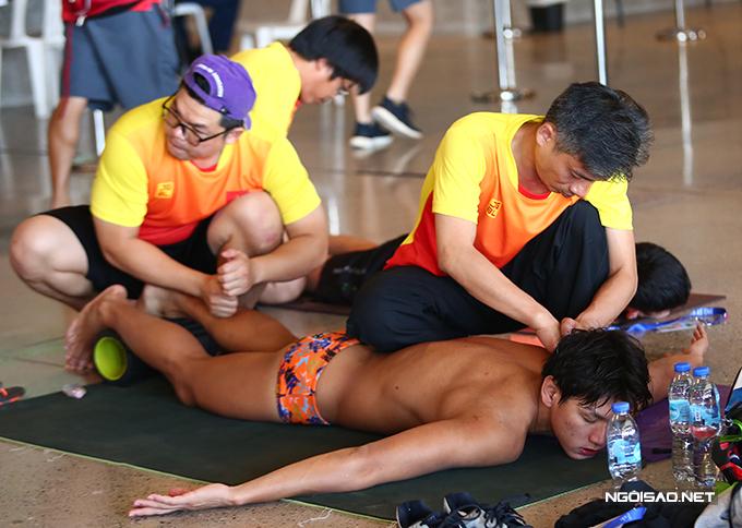 Huy Hoàng được hai bác sĩ massage sau phần thi vòng loại 200m tự do nam sáng 7/12. Ảnh: Đương Phạm.