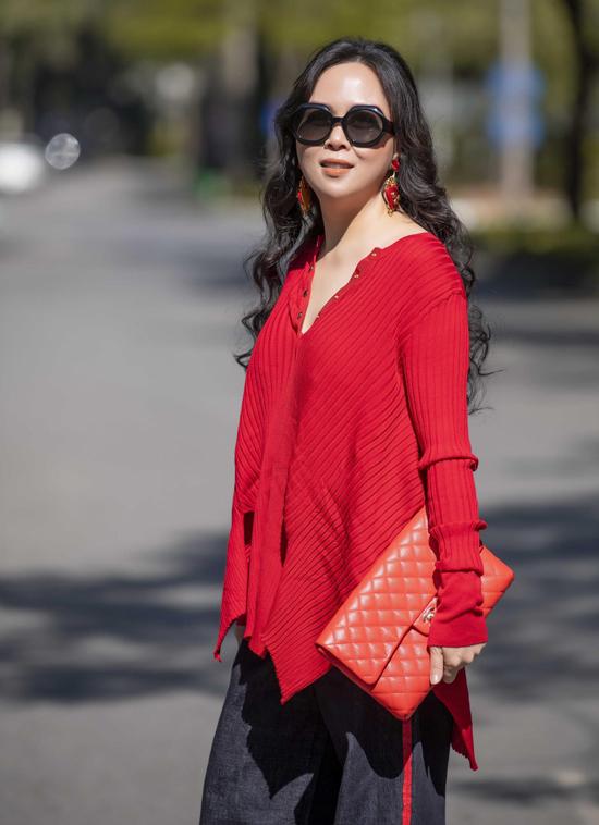 Phượng Chanel phối áo len đỏ, quần jeans ống rộng và túi cầm tay hàng hiệu màu cam. Trông cô nổi bật giữa khung cảnh mùa đông.